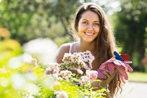 kvinnlig blomsterhandlare i sommarträdgård foto