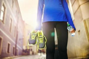 kvinnlig löpare som bär sina skor foto