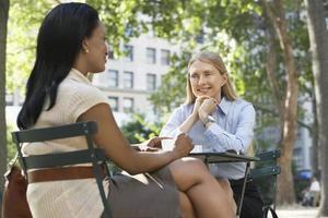 två kvinnliga kollegor på gatukaféet foto