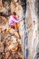 ung kvinnlig bergsklättrare på klippan foto