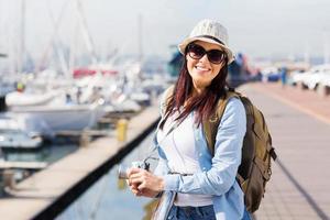 glad kvinnlig turist vid hamnen foto
