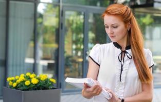 kvinnlig student som går utomhus med boken foto