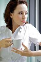 ung kvinna som dricker kaffe på morgonen foto