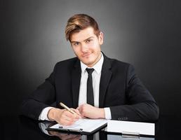 säker affärsman som arbetar vid skrivbordet foto