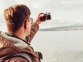 ung man gör selfie på kusten foto