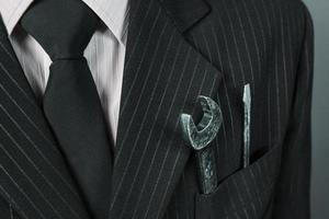 skiftnyckel i en ficka av kostym affärsman foto