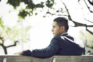 affärsman sitter i bänken parken foto