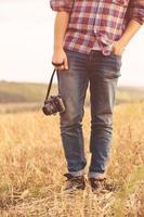 ung man med retro fotokamera utomhus hipster livsstil