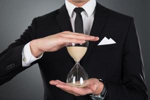affärsman som håller timglas foto