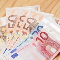 hög med eurosedlar på ett träbord foto