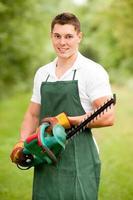 trädgårdsmästare med häcktrimmer foto