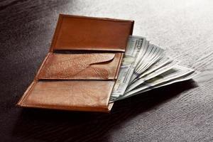 pengar i läderplånbok foto