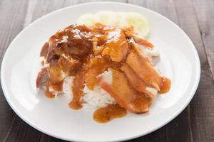 griskött och krispigt fläsk över ris med sött foto
