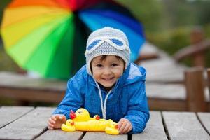 bedårande liten pojke, leker med gummi änder utanför foto