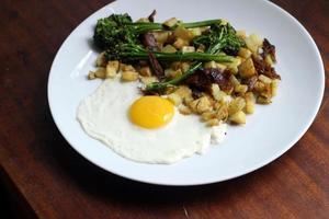 anka confit med potatis och soligt sida upp ägg foto