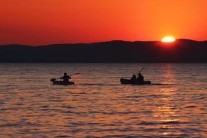 solnedgång över sjön med båtar och ankor foto