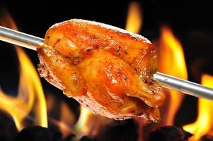 glaserade rotisserie kyckling som rostas över en öppen eld foto