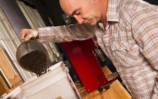 produktionshusägare som väger rostat kaffe för förpackningsdistribution foto