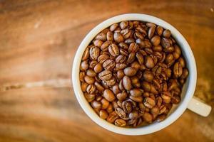 kaffebönor i kopp på grungeträbakgrund foto