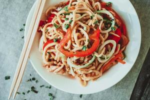 skål med kinesiska nudlar med grönsaker och strimlad kyckling foto