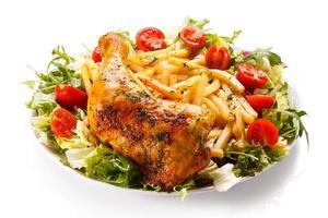 rostade kycklingben, pommes frites och grönsaker foto