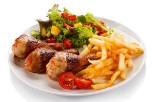 rostade kycklingklubbor, pommes frites och grönsaker foto