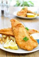 tallrik med fisk och chips på ett träbord foto