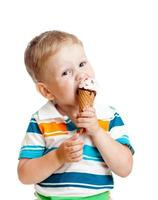 söt unge som äter glass i studio isolerad på vit bakgrund foto