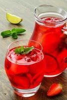 kalla jordgubbar drycker med jordgubbsskivor och mynta foto