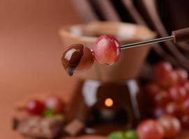 chokladfondue med frukter, på brun bakgrund foto