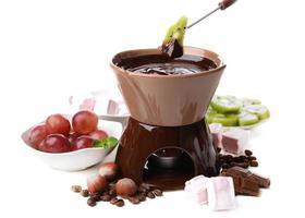 chokladfondue med marshmallow godisar och frukter, isolerad på vitt foto