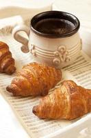 frukost med croissant och kaffekopp foto
