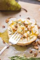 läcker bakad camembert med honung, valnötter, örter och päron foto