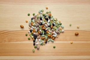 blandade torkade bönor och ärtor på en träbakgrund foto