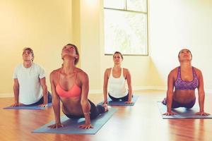 människor som övar kobra utgör i yogaklassen foto
