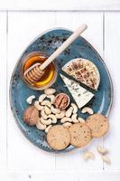 olika typer av ost med honung och nötter. ostplatta. foto