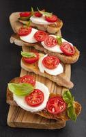 italiensk bruschetta med körsbärstomater, mozzarella & färsk basi foto