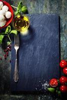 körsbärstomater, basilikablad, mozzarellaost och olivolja f foto