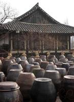 kimchi krukor framför ett traditionellt koreanskt hem foto