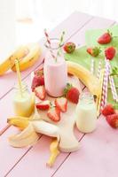 mjölk med färska jordgubbar och bananer foto