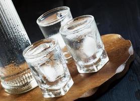 en flaska vodka och glas fulla med is foto