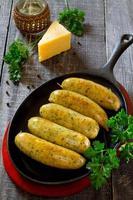 grillade korvar och ost i en stekpanna foto
