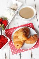 frukost med croissanter, jordgubbar och kopp kaffe på vitt foto