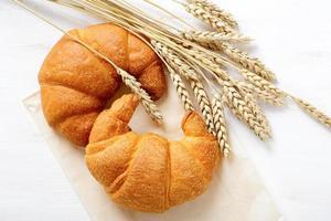 krispig fransk croissant med spikelets av vete foto