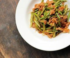 röd curry pasta med brodböna på träplatta.