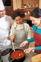 glada kvinnor och kock kocken lagar mat i köket foto