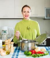 kvinnlig matlagning soppa foto