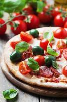 italiensk varm pizza med salami, oliv och tomat