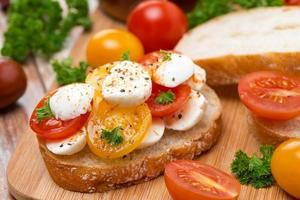 ciabatta med mozzarella och färgglada körsbärstomater foto