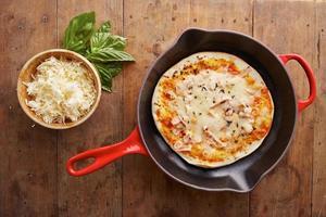kokta mozzarella- och skinkapizza på en stekpanna foto